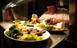 chef plating up a steak meal